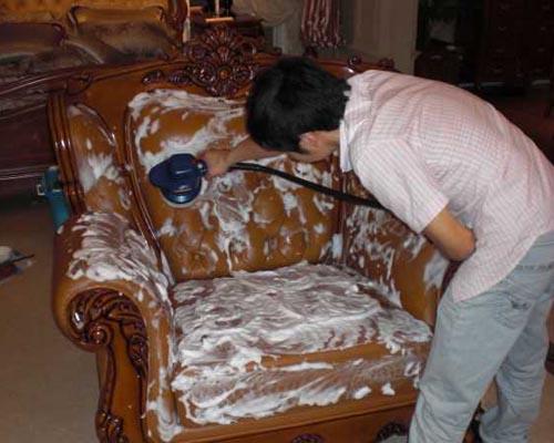 保洁员用设备清洗沙发