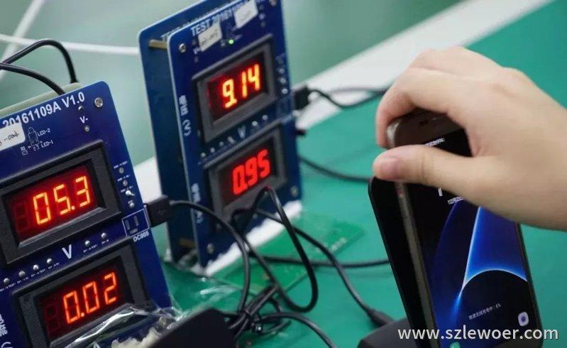 无线充电器厂家工人正在用一台三星的无线充手机进行出厂真机实测